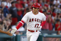 Los Angeles Angels' Shohei Ohtani, of Japan, is congratulated by third base coach Dino Ebel after hitting a home run during the first inning of a baseball game against the Seattle Mariners, Saturday, Sept. 15, 2018, in Anaheim, Calif. (AP Photo/Jae C. Hong)