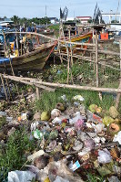 Garbage, including dumped plastic products, piles up on the shore of a tributary of the Mekong River in the southern Vietnamese province of Soc Trang on Aug. 22, 2018. (Mainichi)