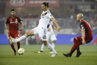Los Angeles Galaxy forward Zlatan Ibrahimovic (9) controls the ball against Toronto FC midfielder Michael Bradley (4) during the first half of an MLS soccer game, on Sept. 15, 2018 in Toronto. (Cole Burston/Canadian Press via AP)