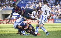 FC Barcelona's Ousmane Dembele, top, and Luis Suarez, below, are seen in action during the Spanish La Liga soccer match between Real Sociedad and FC Barcelona at the Anoeta stadium, in San Sebastian, northern Spain, on Sept. 15, 2018. (AP Photo/Jose Ignacio Unanue)