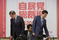 Prime Minister Shinzo Abe, right, and his Liberal Democratic Party presidential opponent Shigeru Ishiba, prepare to sit down during a joint press conference at the LDP headquarters in Tokyo's Chiyoda Ward, on Sept. 10, 2018. (Mainichi)