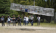 In this June 3, 2017 file photo, Tsubasa Nakamura, project leader of Cartivator, third from left, watches the flight of the test model of the flying car on a former school ground in Toyota, Aichi Prefecture. (AP Photo/Koji Ueda)