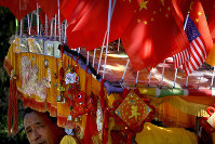 In this Sept. 16, 2018 photo, a driver looks out from his trishaw decorated with an American flag and Chinese flags in Beijing. (AP Photo/Andy Wong)