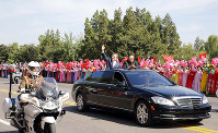 South Korean President Moon Jae-in, left, waves with North Korean leader Kim Jong Un from a car during a parade through the streets, in Pyongyang, North Korea, on Sept. 18, 2018. (Pyongyang Press Corps Pool via AP)