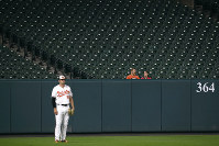 A pair of spectators sits in outfield seats behind Baltimore Orioles left fielder Trey Mancini in the first inning of a baseball game between the Orioles and the Toronto Blue Jays, on Sept. 17, 2018, in Baltimore. (AP Photo/Patrick Semansky)