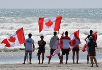 Team Canada members hold Canadian flags during the World Surfing Games in the city of Tahara, Aichi Prefecture, on Sept. 17, 2018. (Mainichi)
