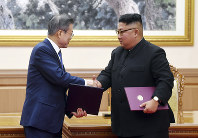 South Korean President Moon Jae-in, left, and North Korean leader Kim Jong Un shakes hands after signing the documents at the Paekhwawon State Guesthouse in Pyongyang, North Korea, on Sept. 19, 2018.  (Pyongyang Press Corps Pool via AP)