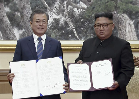 In this image made from video provided by Korea Broadcasting System (KBS), South Korean President Moon Jae-in, left, and North Korean leader Kim Jong Un pose after signing documents in Pyongyang, North Korea on Sept. 19, 2018.(Korea Broadcasting System via AP)