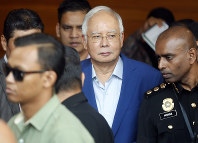 In this May 22, 2018 file photo, former Malaysian Prime Minister Najib Razak, center, arrives at the Anti-Corruption Agency for questioning in Putrajaya, Malaysia. (AP Photo/Vincent Thian)