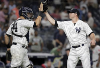 New York Yankees relief pitcher Zach Britton, right, celebrates with catcher Gary Sanchez after the Yankees defeated the Boston Red Sox 3-2 during a baseball game on  Sept. 18, 2018, in New York. (AP Photo/Julio Cortez)