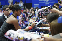 Naomi Osaka of Japan signs her autograph for fans after defeating Dominika Cibulkova of Slovakia during the second round match of Pan Pacific Open women's tennis tournament in Tokyo, on Sept. 19, 2018. (AP Photo/Eugene Hoshiko)