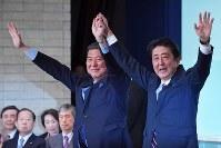 自民党総裁に選ばれ、石破茂元幹事長(左)と手を取り合って議員らの声援にこたえる安倍晋三首相=東京都千代田区の同党本部で2018年9月20日午後2時21分、渡部直樹撮影