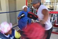 コーチのミットめがけてパンチを打ち込むおばあちゃん=ヨハネスブルクで2018年9月13日、小泉大士撮影