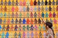 人の形をした色とりどり、さまざまな柄のペンケースが壁いっぱいに並ぶ=京都市右京区で、川平愛撮影