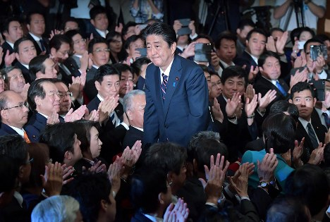 Prime Minister Shinzo Abe stands up and bows after his re-election as president of the ruling Liberal Democratic Party is announced at the party's headquarters in central Tokyo on Sept. 20, 2018. (Mainichi/Naoki Watanabe)