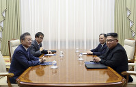 South Korean President Moon Jae-in, left, and North Korean leader Kim Jong Un, right, attend their summit as South Korea's National Intelligence Service Director Suh Hoon, second from left, and North Korean senior ruling party official and former intelligence chief, Kim Yong Chol, second from right, sit at the Paekhwawon State Guesthouse in Pyongyang, North Korea, Wednesday, Sept. 19, 2018. (Pyongyang Press Corps Pool via AP)