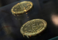 In this Dec. 8, 2017, file photo, coins are displayed next to a Bitcoin ATM in Hong Kong. (AP Photo/Kin Cheung)