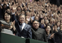 South Korean President Moon Jae-in, second from left, his wife Kim Jung-sook, left, North Korean leader Kim Jong Un, second from right, and his wife Ri Sol Ju, greet each other upon their arrival before the mass games performance of