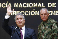 Colombia's President Ivan Duque, left, waves next to the Commander of the Armed Forces Gen. Alberto Mejia, during a press conference at police headquarters in Bogota, Colombia, on Sept. 19, 2018. D (AP Photo/Fernando Vergara)