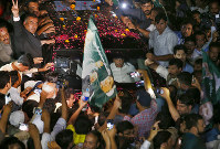 A vehicle carrying former Pakistani Prime Minister Nawaz Sharif is surrounded by his supporters following his release from prison in Rawalpindi, Pakistan, on Sept. 19, 2018. (AP Photo/Anjum Naveed)