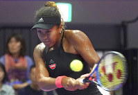Naomi Osaka of Japan returns a shot against Dominika Cibulkova of Slovakia during the second round of Pan Pacific Open women's tennis tournament in Tokyo on Sept. 19, 2018. (AP Photo/Eugene Hoshiko)