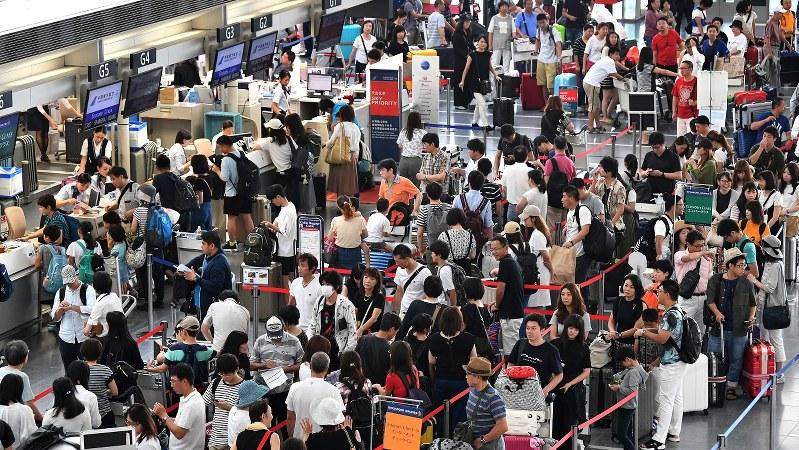 海外に向かう人たちで混雑する国際線の出発カウンター=愛知県常滑市の中部国際空港で2018年8月10日、大西岳彦撮影