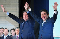 Prime Minister Shinzo Abe, right, holds up a hand of former Liberal Democratic Party Secretary-General Shigeru Ishiba after beating him in the party presidential election, at the party's headquarters in Tokyo's Chiyoda Ward, on Sept. 20, 2018. (Mainichi/Naoki Watanabe)