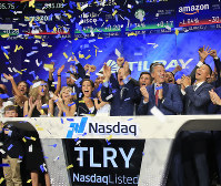 In this July 19, 2018 file photo, Brendan Kennedy, third from right in front, CEO and founder of British Columbia-based Tilray Inc., a major Canadian marijuana grower, leads cheers as confetti falls to celebrate his company's IPO (TLRY) at Nasdaq in New York. (AP Photo/Bebeto Matthews)