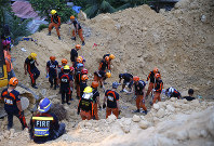 Rescuers dig through the rubble to search for possible survivors following a landslide that buried dozens of homes in Naga city, Cebu province central Philippines on Sept. 20, 2018. (AP Photo/Bullit Marquez)