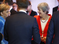 German Chancellor Angela Merkel, left, and British Prime Minister Theresa May talk prior to the beginning of the plenary session of the informal EU summit in Salzburg, Austria, on Sept. 20, 2018. (AP Photo/Matthias Schrader)