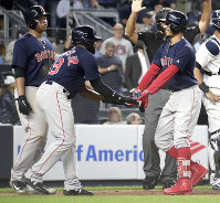Boston Red Sox's Mookie Betts, right, is greeted at home plate by Jackie Bradley Jr. (19) and Rafael Devers, left, after he drove them in on a three-run home run off New York Yankees relief pitcher Aroldis Chapman during the eighth inning of a baseball game on Sept. 20, 2018, in New York. (AP Photo/Julio Cortez)