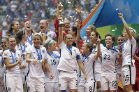 In this, July 5, 2015 file photo, the United States Women's National Team celebrates with the trophy after they beat Japan 5-2 in the FIFA Women's World Cup soccer final in Vancouver, British Columbia, Canada. (AP Photo/Elaine Thompson)