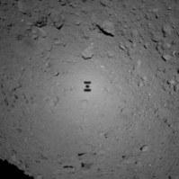 小型探査ロボットの投下に向け降下中、リュウグウに映ったはやぶさ2の影(中央)=JAXA提供