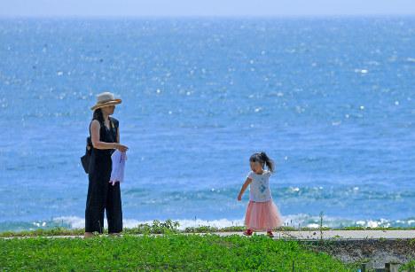 海水浴の父との思い出がつまった大谷海岸に、今年初めて娘の菜由ちゃんを連れてきた三浦幸子さん(左)。「父を奪った海を見ることができなかったのですが。娘には海を嫌いになってほしくはないんです」=宮城県気仙沼市本吉町で2018年8月22日、梅村直承撮影