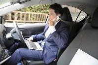 カーシェアリングの車両を利用して得意先に電話をかける生命保険会社の営業マン=東京都立川市で2018年8月30日午後4時、松本尚也撮影