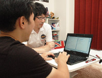 ひきこもりの男性(手前)を相手にプログラミングを教える重金晋さん=徳島市で、大久保昂撮影