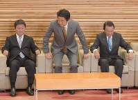 Prime Minister Shinzo Abe takes his seat at a Cabinet meeting on Sept. 21, 2018 at the prime minister's office in central Tokyo, flanked by Deputy Prime Minister and Finance Minister Taro Aso, right, and Toshimitsu Motegi, minister for economic revitalization. (Mainichi/Masahiro Kawada)