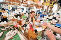 Chisae Washizawa works at a pay desk with a loud voice at Tsukiji fish market in Tokyo's Chuo Ward, on Aug. 28, 2018. (Mainichi/Naoki Watanabe)