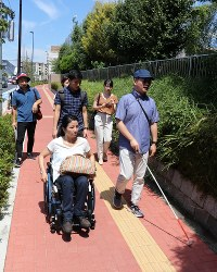 Paralympians Association of Japan chairman Junichi Kawai, right, and others check the textured paving blocks for the blind or visually impaired and other areas around the second National Training Center on Aug. 26, 2018, in Tokyo's Kita Ward. (Mainichi)
