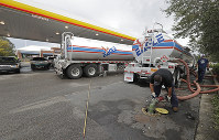 In this Sept. 17, 2018, file photo people wait in line as Travis Hall, right, and Brandon Deese, back, pump fuel from two tanker trucks at a convenience store in Wilmington, N.C. (AP Photo/Chuck Burton)