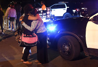In this Sept. 20, 2018, photo women hug at the scene where several people were shot, including a child, during a memorial service outside a home in Syracuse, N.Y. (Dennis Nett /The Post-Standard via AP)