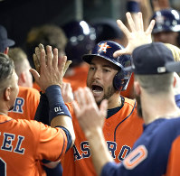 Houston Astros' George Springer celebrates in the dugout after hitting a three-run home run against the Los Angeles Angels during the eighth inning of a baseball game on Sept. 21, 2018, in Houston. (AP Photo/David J. Phillip)