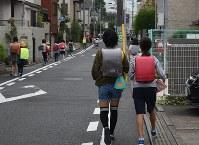 手提げかばんや巾着袋に教材を入れて登校する児童=東京都杉並区で20日、篠原成行撮影