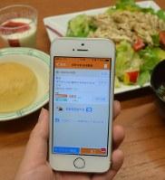 この日の社員食堂のメニュー「ゴマたっぷり鶏ささみのサラダランチ」を選ぶと、摂取カロリーや糖質量がアプリ画面に表示される=東京都中央区の味の素本社で