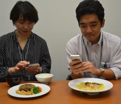 社員食堂のメニューをアプリに入力する中村実里さん(左)と篠村悠木さん=東京都中央区の味の素本社で