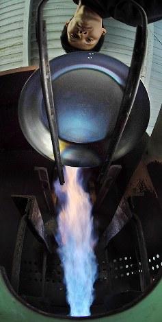 食材のこびりつきを防ぐため、約700度の熱で一つ一つ焼き入れ作業を行っている=大阪府八尾市の「藤田金属」で、山田尚弘撮影