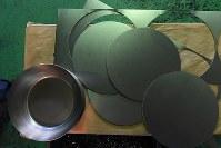 鉄の板(右)を丸く打ち抜き、職人の手が加わりフライパンの形になる=大阪府八尾市の「藤田金属」で、山田尚弘撮影