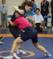 レスリング教室で6年生児童からタックルを受ける吉田沙保里選手(左)=千葉県松戸市の相模台小学校で2018年9月22日午前9時57分、橋口正撮影