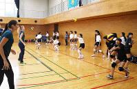 カザフスタンの選手(左)を相手にレシーブの練習をする参加者たち=奈良県橿原市で、藤原弘撮影
