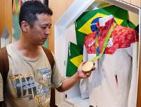 リオデジャネイロ五輪で田中佑典選手が獲得した金メダルを手にする来館者=和歌山市本町2のわかやまスポーツ伝承館で、木原真希撮影